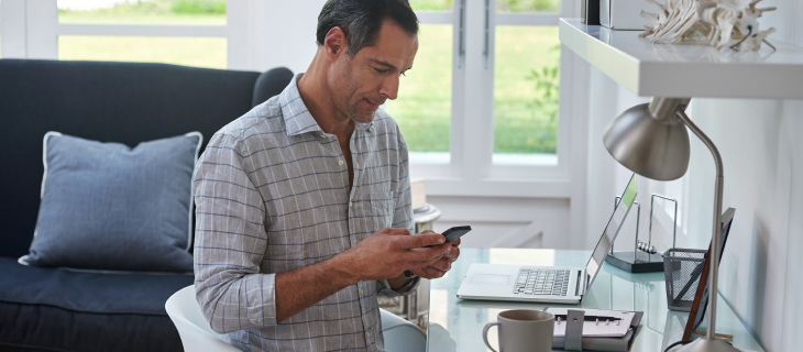 A mature man working from home looking at his cell phone.