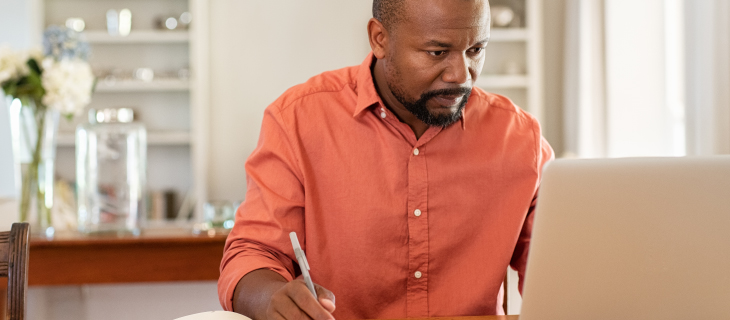 A mature man holding a pen in his hand taking notes while working on a laptop in the kitchen.