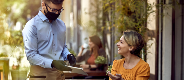 Woman sitting at a table with a waiter wearing personal protective gear delivering her a menu.
