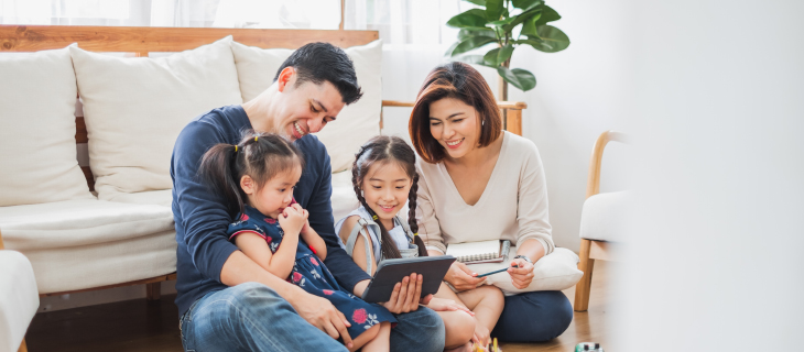A family sitting on living room floor, looking at a tablet.