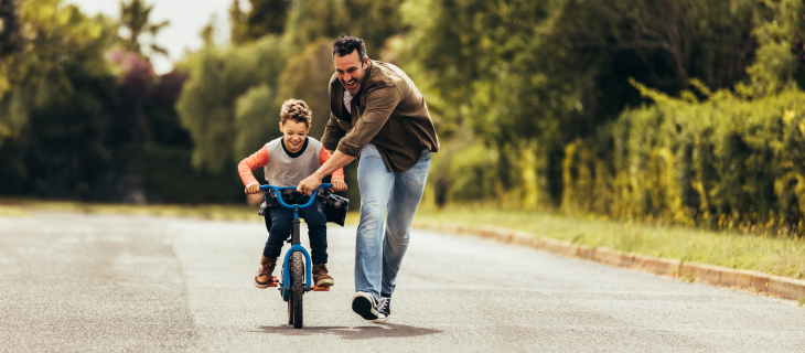 A father teaching his son how to ride a bike.