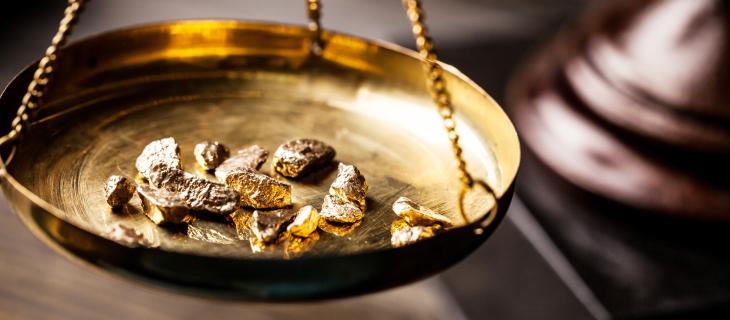Pieces of gold on a suspended scale plate.