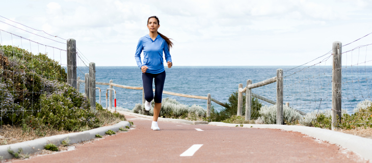 An athletic woman is jogging on a paved road alongside the ocean.