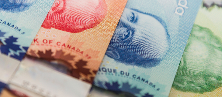 Canadian paper money, red, blue, green bill with Bank of Canada signature facing upwards.