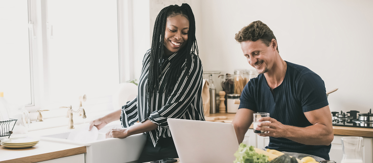 A couple laughing in the kitchen, while the man is working on his laptop and the woman is washing the dishes.