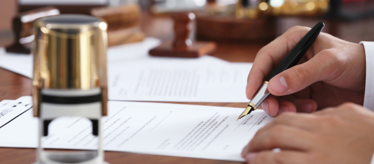 A hand using a fountain pen to sign documents at a desk.