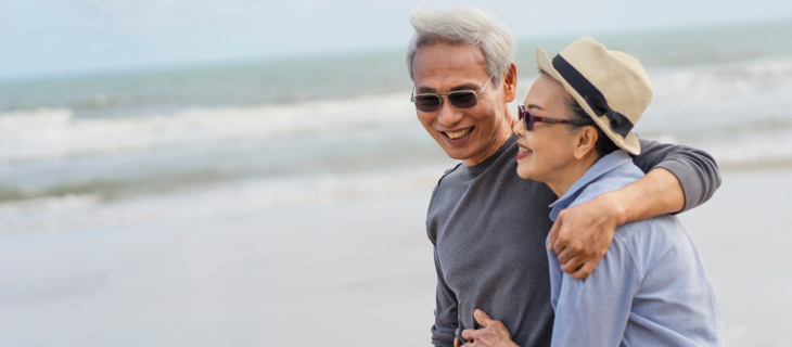 Elderly couple laughing while walking on the beach.