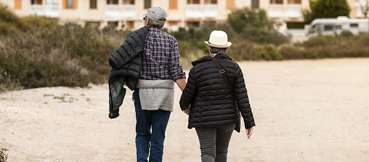 An older couple holding hands walking on the beach.