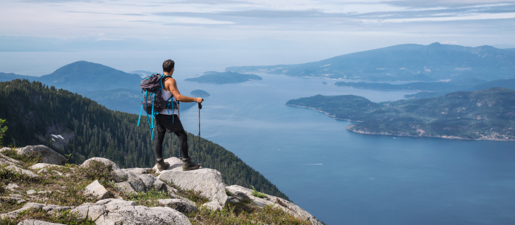 Man hiking standing at the top of a mountain overlooking the scenery, of mountains and water.