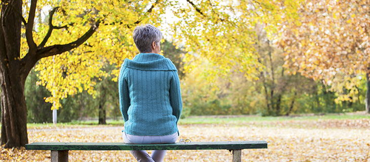 An elder woman sitting on a bench looking at the fall leaves.