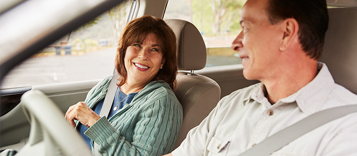 A mature couple in a car looking at each other smiling.