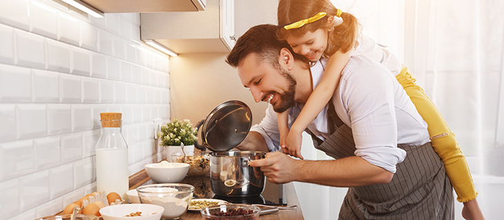 Father with daughter on his back, cooking together in the kitchen.