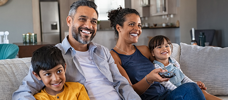 A family with two young children sitting on a couch watching television and laughing.  watching television, laughing.