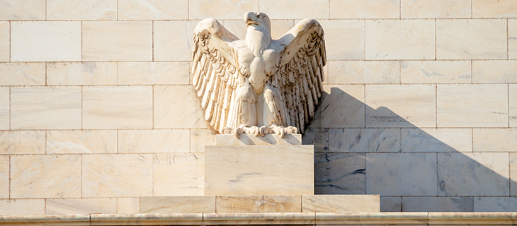 Statue of a bald eagle made in stone on a building.