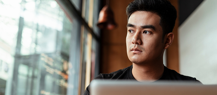 Student looking outside the window and working from laptop