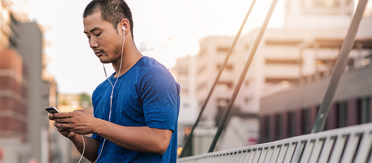A student wearing earphones using his mobile phone.