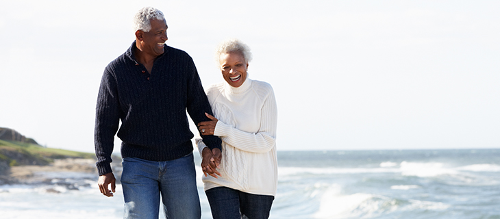 An older couple walking by the ocean holding hands.