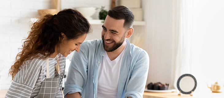 Young couple laughing while cooking in the kitchen