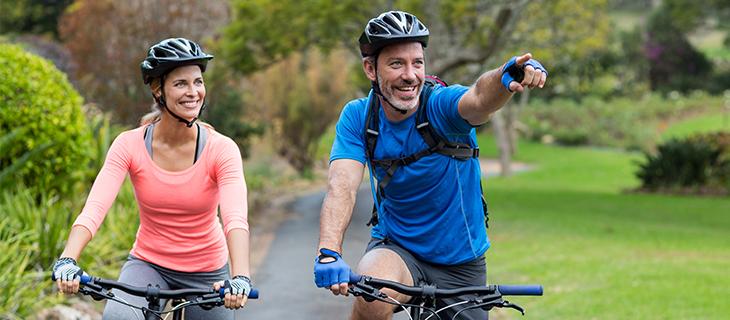 A mature couple biking outdoors.