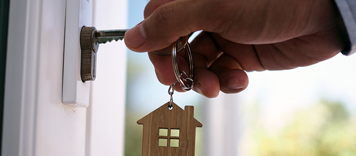 A hand unlocking a door with a key that has a wooden house keychain on it.