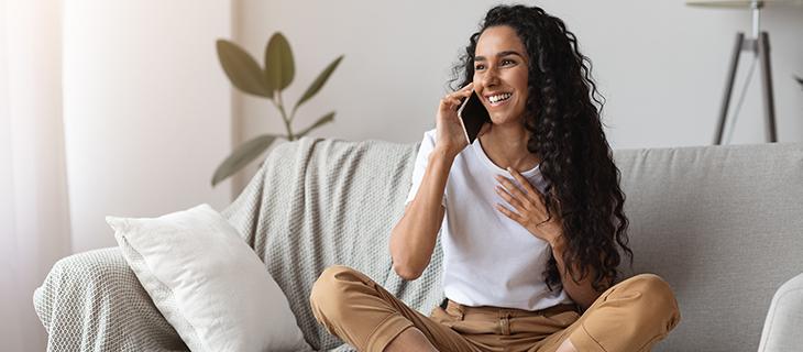 Une femme souriante en parlant sur son téléphone portable assise sur un canapé.