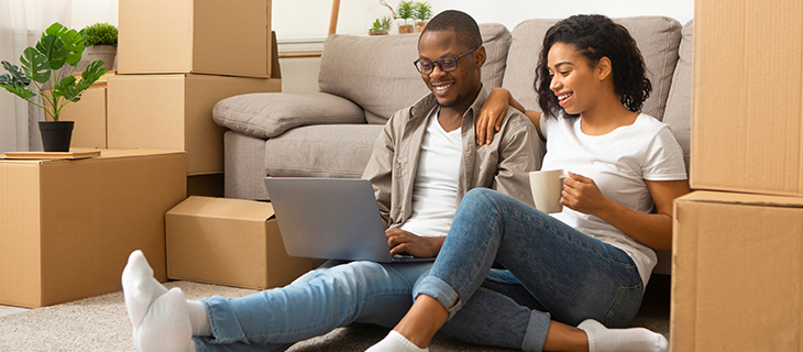 Young couple moving into a new home and looking into a laptop for house designs