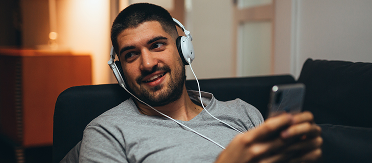 A young man holding his cell phone with head phones on.