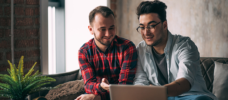 same-sex male couple drinking coffee and looking into laptop screen