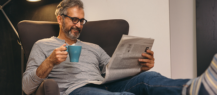 An eldery man relaxing on a lounge chair reading a newspaper .