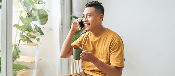 Young man talking on a mobile phone and drinking coffee by a window