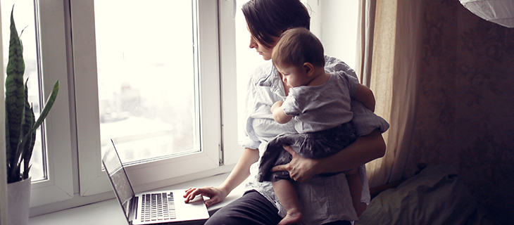 Mom with a baby in her arms working on a laptop near the window
