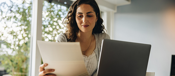 Woman reading some document while working on laptop