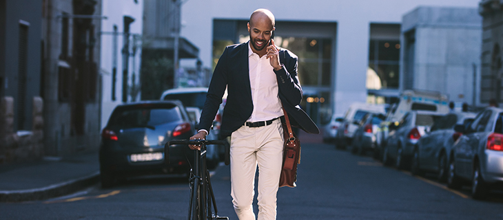 businessman walking outdoors with a bicycle and talking on mobile phone