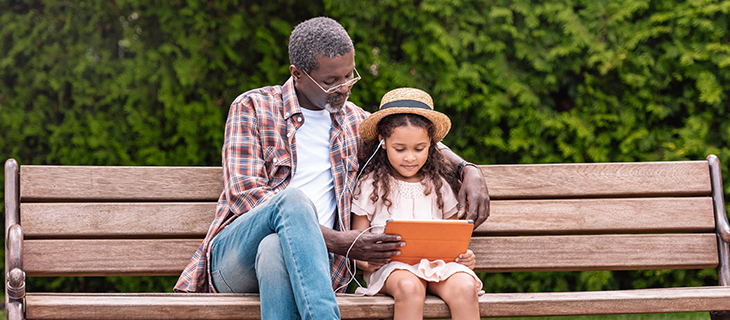 Father and daughter sitting on a bark bench and watching a video on a digital tablet