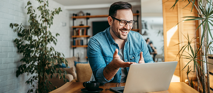 Portrait of a cheerful man having a video call on laptop