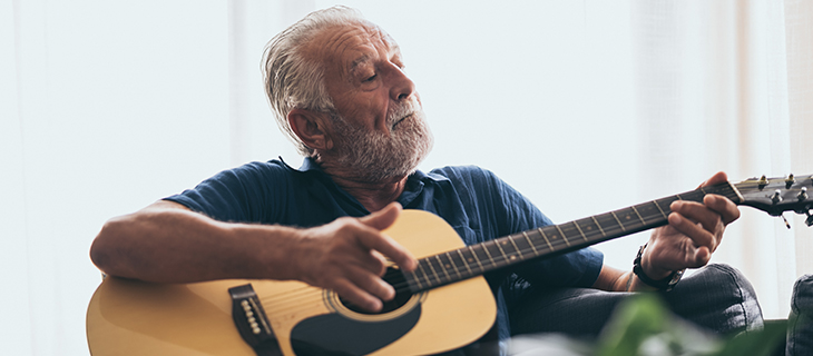 Older man playing the guitar in his house