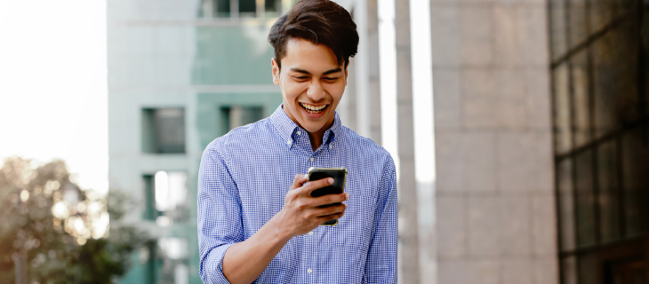 A young man  laughing while looking at his mobile telephone.