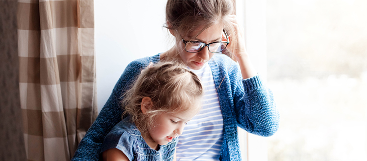 Mother and young daughter sitting by the window and reading from laptop