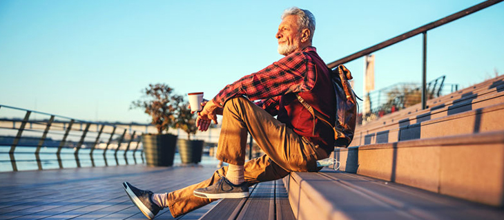 Pensive older man sitting outdoors with backpack and coffee cup in his hand