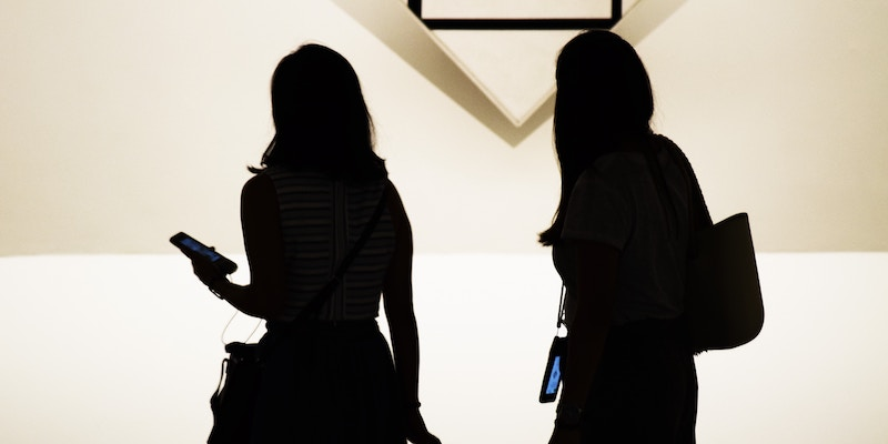 Silhouette of two people holding phones