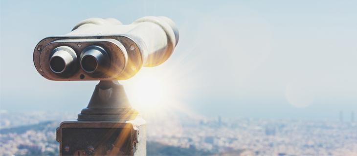 Jumelle regardant un pays à une vue élevée avec le soleil qui brille dans lentille.