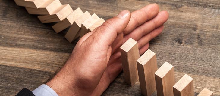 Une main divisant des blocs en bois.