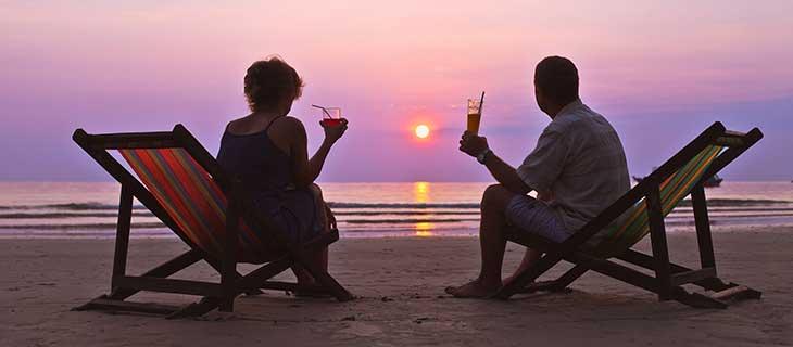 Une femme et un homme âgé assis près de l'océan regardant le couche du soleil.