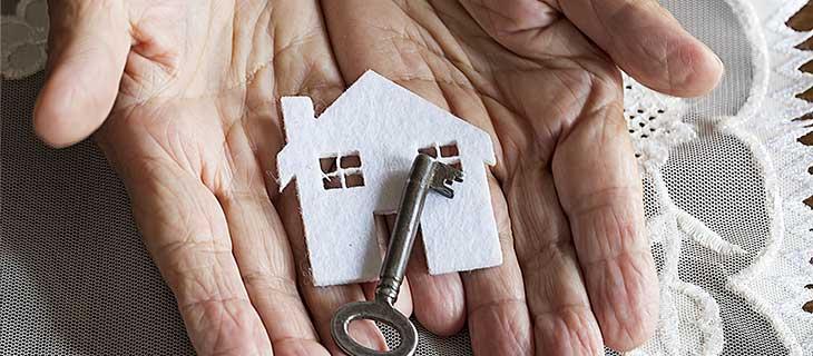 Des vieilles mains présentant une découpe d'une maison avec une clé en métal.