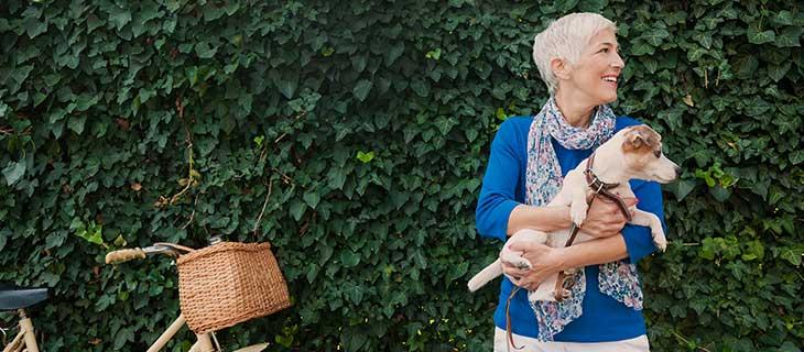 Madame mature tenant un chien dehors, à cotés d'une bicyclette.