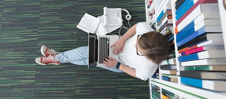 Un étudiant assis sur le plancher d'une bibliothèque avec son portable.