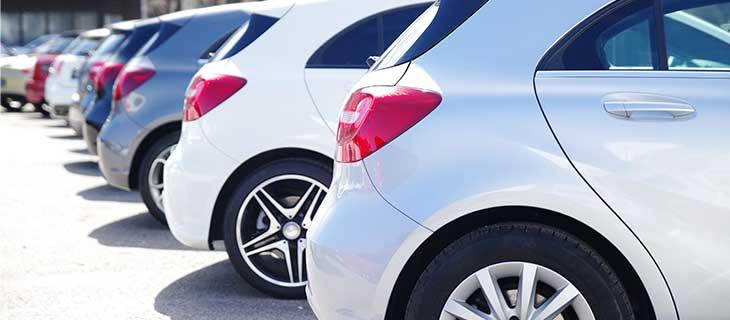 Une vue sur les pare-chocs de nombreux véhicules dans un stationnement.