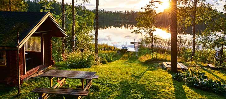 Un chalet en bois peinturé rouge au bord d'un lac avec un bateau près d'un quai donnant sur le coucher du soleil.