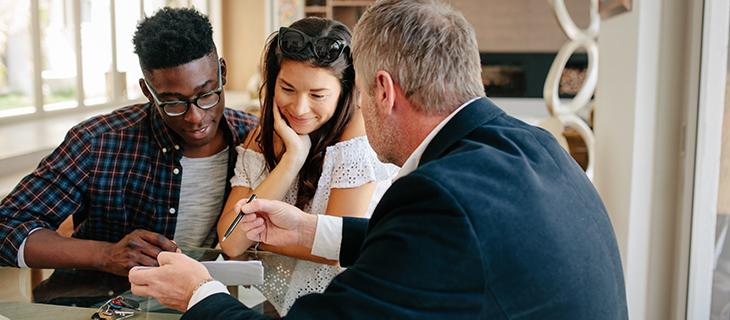 Conseillé financier tenant un stylo, en montrant un contrat à un jeune couple.