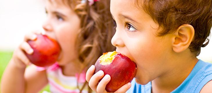 Des enfants qui mangent des pommes.